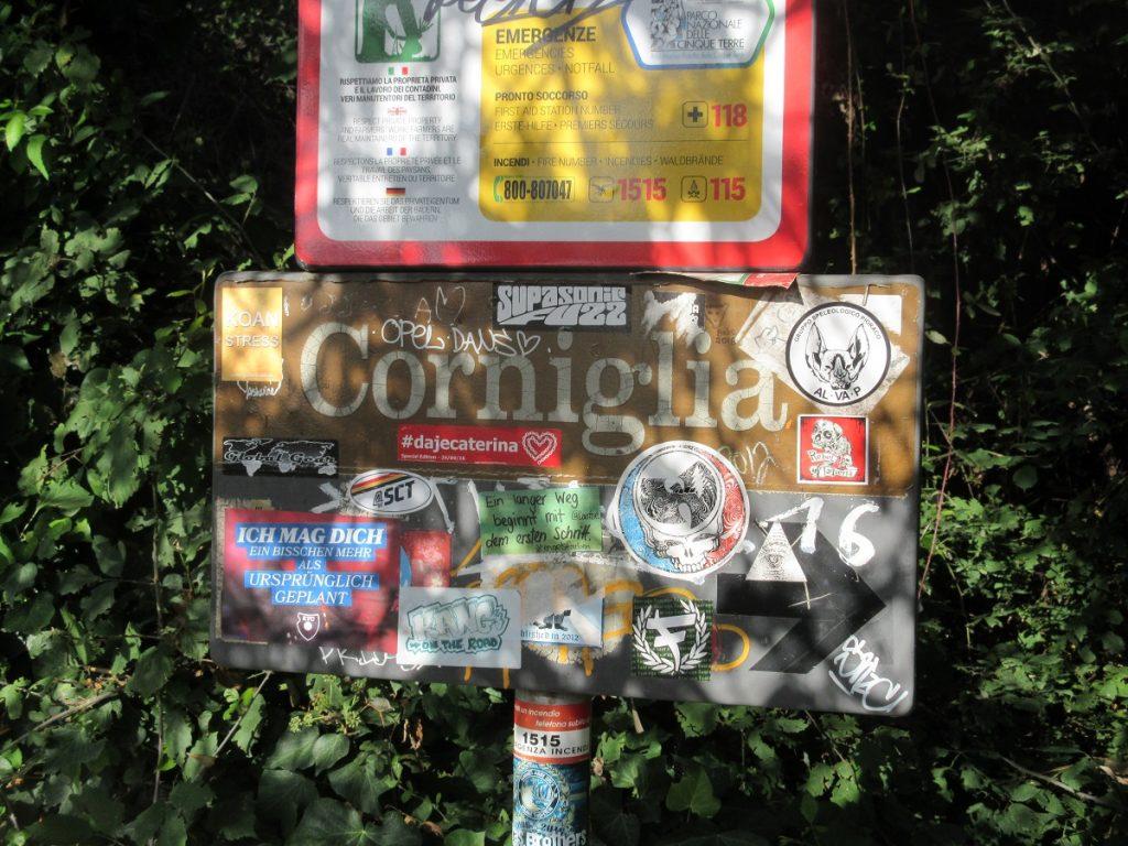 Bunt beklebte Hinweisschilder in aller Länder Sprachen kündigen beim Wandern in der Cinque Terre Corniglia an!