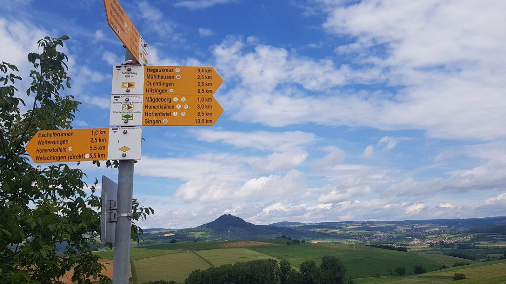 Gelbe Wegmarkierungen vor blauem Himmel im Hegau