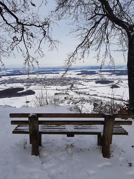 verschneite Sitzbank aus Holz