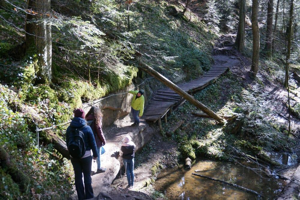 Menschen an Holzbrücke in Schlucht